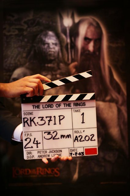 """A Bonhams employee holds a clapper board from """"The Lord of the Rings"""" movie trilogy on July 31, 2014 in London, England. The board wrapped the very last scene that Sir Christopher Lee filmed in the third and final film The Return of the King and is estimated at $6000-8000. It forms part of Bonhams """"There's No Place Like Hollywood"""" movie memorabilia auction taking place in New York on November 24, 2014. (Photo by Peter Macdiarmid/Getty Images)"""