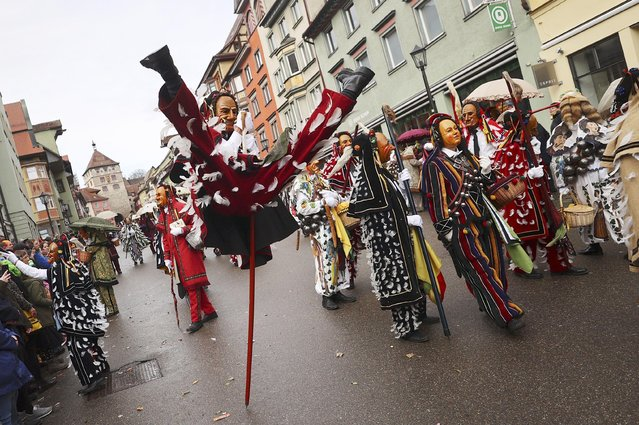 A carnival reveller in a traditional costume vaults on his pole during the fool jump (Narrensprung) parade in Rottweil, Germany, February 24, 2020. (Photo by Kai Pfaffenbach/Reuters)