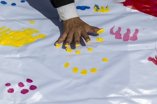 A man leaves finger prints on a banner for the victims killed in Monday's bomb blast during a religious ceremony near at the Erawan shrine, the site of Monday's deadly blast, in central Bangkok, Thailand, August 21, 2015. (Photo by Athit Perawongmetha/Reuters)