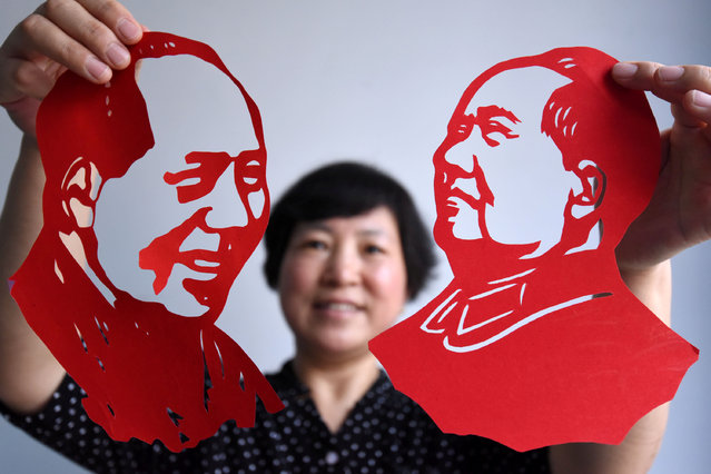 A local artist presents a Chinese paper-cut of Chairman Mao which she made to celebrate the 95th anniversary of the foundation of Communist Party of China in Handan, Hebei Province, China, June 30, 2016. (Photo by Reuters/China Daily)