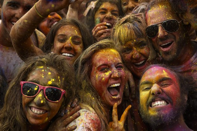 Revelers of the Holi Festival of Colours pose for a selfie,  covered in coloured powder,  in Madrid, Spain, Saturday, August 9, 2014. The festival is fashioned after the Hindu spring festival Holi, which is mainly celebrated in the north and east of India. (Photo by Daniel Ochoa de Olza/AP Photo)