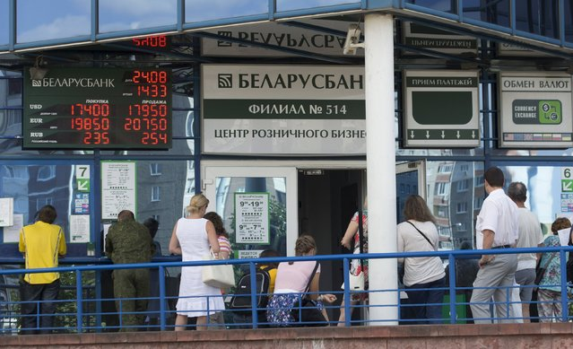 People wait in a queue outside a branch of Belarusbank in Minsk, August 24, 2015. The Belarussian rouble weakened by around 5 percent on Monday to 17.601 to the dollar, according to central bank data, coming under pressure from currency volatility in Russia and elsewhere. (Photo by Vasily Fedosenko/Reuters)