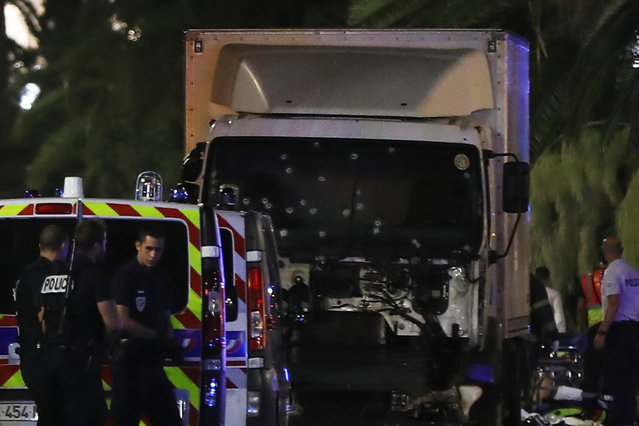"""Police officers stand near a van, with its windscreen riddled with bullets, that ploughed into a crowd leaving a fireworks display in the French Riviera town of Nice on July 14, 2016. Up to 30 people are feared dead and over 100 others were injured after a van drove into a crowd watching Bastille Day fireworks in the French resort of Nice on July 14, a local official told French television, describing it as a """"major criminal attack"""". (Photo by Valery Hache/AFP Photo)"""