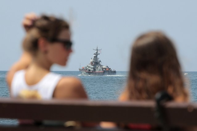 People spend time at a quay, with a Russian warship seen in the background, in Sevastopol in Crimea August 8, 2014. Russian President Vladimir Putin, senior government officials and many lawmakers will visit Crimea this week, two sources told Reuters, in a defiant show of support for Russia's annexation of the Black Sea region despite tough new Western economic sanctions. (Photo by Pavel Rebrov/Reuters)