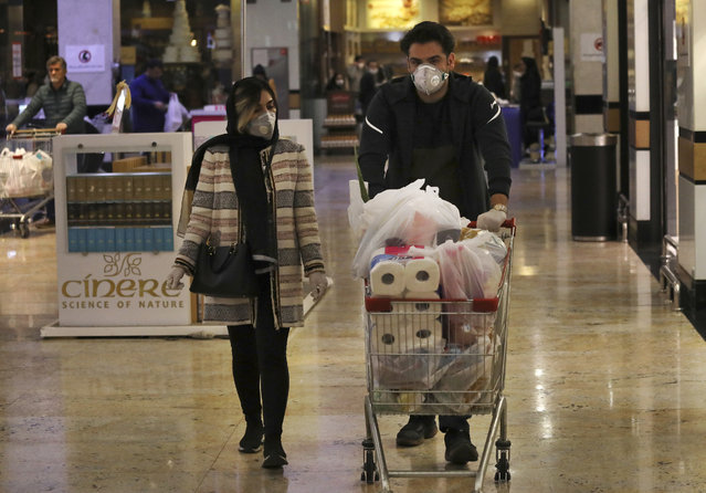 Shoppers wearing face masks and gloves stock up on supplies at the Palladium Shopping Center, in northern Tehran, Iran, Tuesday, March 3, 2020. Iran's supreme leader put the Islamic Republic's armed forces on alert Tuesday to assist health officials in combating the outbreak of the new coronavirus, the deadliest outside of China. (Photo by Vahid Salemi/AP Photo)