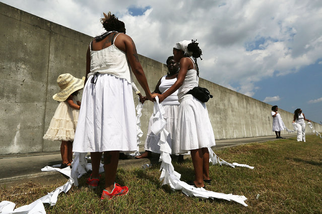 People hold hands along the repaired levee wall in the Lower Ninth Ward during a ceremony marking the 10th anniversary of Hurricane Katrina on August 29, 2015 in New Orleans, Louisiana. (Photo by Mario Tama/Getty Images)