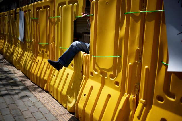 A man gets in through barrier, which have been built to block buildings from a street after the lockdown was lifted in Wuhan, capital of Hubei province and China's epicentre of the novel coronavirus disease (COVID-19) outbreak, April 13, 2020. (Photo by Aly Song/Reuters)