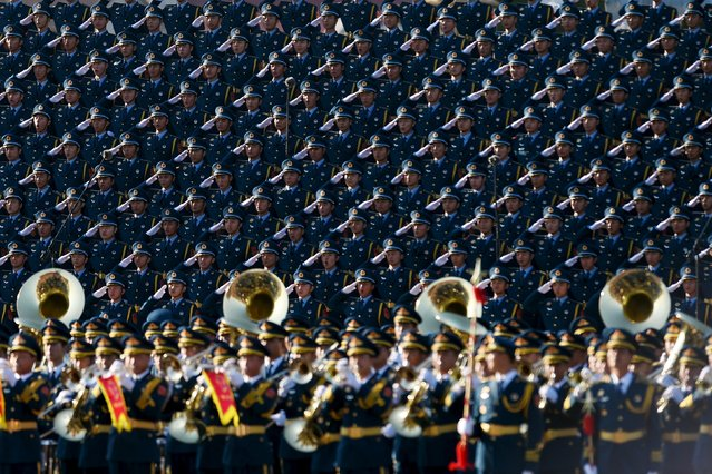 Chinese soldiers salute in a chorus on a stage during a military parade at Tiananmen Square in Beijing on September 3, 2015, to mark the 70th anniversary of victory over Japan and the end of World War II. (Photo by Wang Zhao/Reuters)