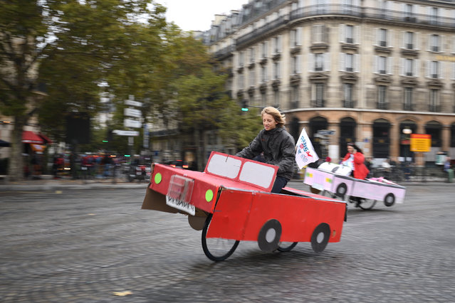 """People ride a cardboard car on Place de la Bastille during a """"car free"""" day in Paris on October 1, 2017. Parisians were encouraged to roller-blade, bike or stroll through the City of Light for a """"car-free"""" day intended to leave the streets vacant for slower, clean forms of transport. October 1, marks the third time the French capital has experimented with a car ban, but it is by far the most ambitious with the zone set aside for pedestrians or cyclists covering the entire historic heart of the city – 105 square kilometres (40 square miles). (Photo by Eric Feferberg/AFP Photo)"""