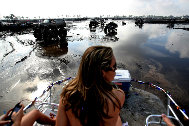 """Jessica Reynolds of West Palm Beach sits atop the swamp buggy """"Killing a Little Time"""" as it cruises through the mud bog. (Photo by Gary Coronado/The Palm Beach Post)"""