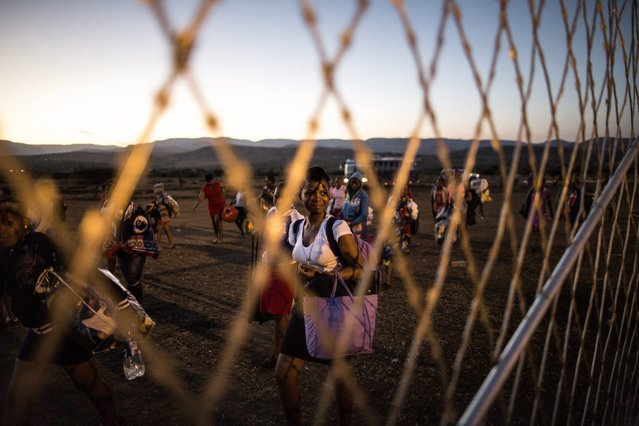A woman looks towards the fence as hundreds of South African maidens arrive on September 4, 2014 at the eNyokeni Royal Palace in Nongoma in the KwaZulu-Natal region for the 13th anniversary of the Reed Dance (uMkhosi woMhlanga) celebrated by the Zulu King Goodwill Zwelithin on September 5. (Photo by Marco Longari/AFP Photo)
