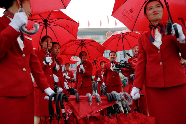 Ushers manage umbrellas used by delegates arriving for the opening session of the 19th National Congress of the Communist Party of China at the Great Hall of the People in Beijing, China on October 18, 2017. (Photo by Damir Sagolj/Reuters)