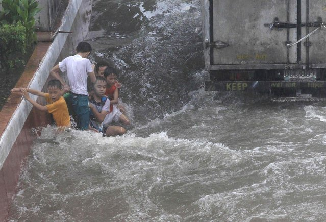 Children play in a flooded area after tropical storm Fung-Wong battered metro Manila September 19, 2014. (Photo by Romeo Ranoco/Reuters)