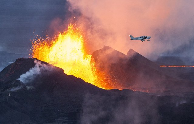 An aerial picture taken on September 14, 2014 shows a plane flying over the Bardarbunga volcano spewing lava and smoke in southeast Iceland. The Bardarbunga volcano system has been rocked by hundreds of tremors daily since mid-August, prompting fears the volcano could explode. Bardarbunga, at 2,000 metres (6,500 feet), is Iceland's second-highest peak and is located under Europe's largest glacier, Vatnajoekull. (Photo by Bernard Meric/AFP Photo)