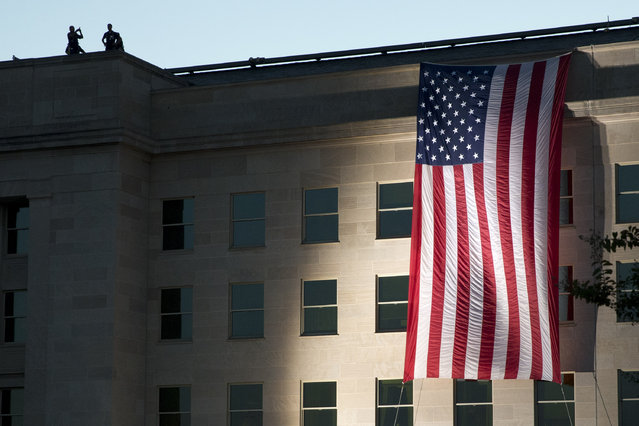 A U.S. flag is draped on the side of the Pentagon, Friday, September 11, 2015, where the building was attacked on September 11th in 2001, on the 14th anniversary of the attack. (Photo by Jacquelyn Martin/AP Photo)
