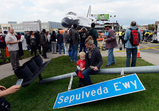 One of hundreds of street signs temporarily removed for the 12-mile road trip of space shuttle Endeavour is used as prop as a family gets their picture taken with the orbiter parked in a mall parking lot in Los Angeles, California. (Photo by Kevork Djansezian)