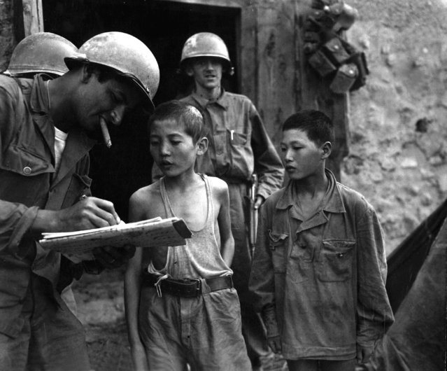 Two North Korean boys, serving in the North Korean Army, taken prisoner in the Sindang-dong area by elements of the 389th Inf. Regt., are interrogated by a U.S. soldier shortly after their capture.  September 18, 1950. (Photo by Pfc. Francis Mullin)