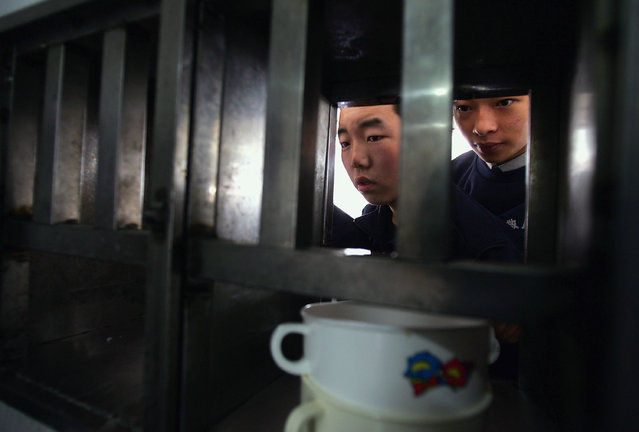Chinese kids wait for their lunch outside an eatery at an assistance center February 23, 2005 in Shenzhen, Guangdong Province, China. (Photo by Cancan Chu/Getty Images)