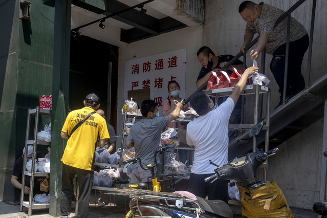 Deliverymen collect food orders in Beijing on Friday, June 19, 2020. China declared a fresh outbreak in Beijing under control after numbers for new cases stabilized as hundreds of thousands are tested. (Photo by Ng Han Guan/AP Photo)
