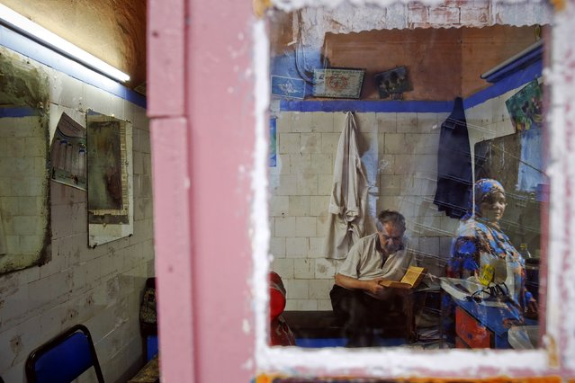 A woman is reflected in the mirror of shop as a barber reads the Koran in Rabat's Medina September 23, 2014. (Photo by Damir Sagolj/Reuters)