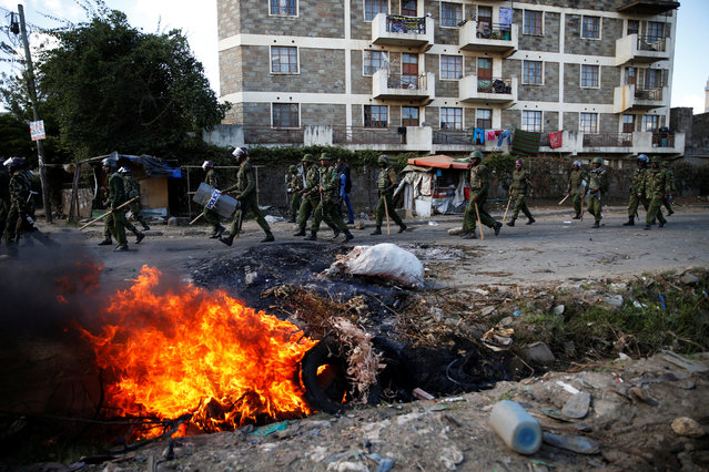 Kenyan police walk past burning tires set on fire during clashes between supporters of Kenyan opposition National Super Alliance (NASA) and police in Nairobi, Kenya, November 28, 2017. (Photo by Baz Ratner/Reuters)