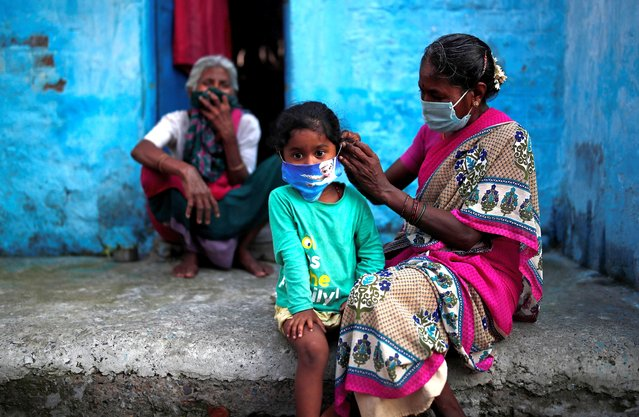 A woman wearing a protective face mask adjusts her daughter's face mask outside their house at a slum area, during an extended nationwide lockdown to slow the spreading of the coronavirus disease (COVID-19), in New Delhi, India, June 24, 2020. (Photo by Adnan Abidi/Reuters)