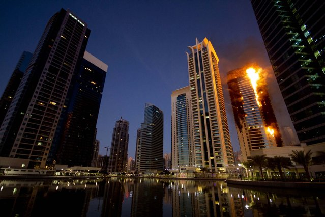 Flames engulf a portion of the Tamweel residential tower at Jumeirah Lakes Towers in Dubai, United Arab Emirates, November 18, 2012. Civil defense officials did not give immediate details on possible casualties or the cause of the predawn fire. (Photo by Kaveh Kashani/Associated Press)