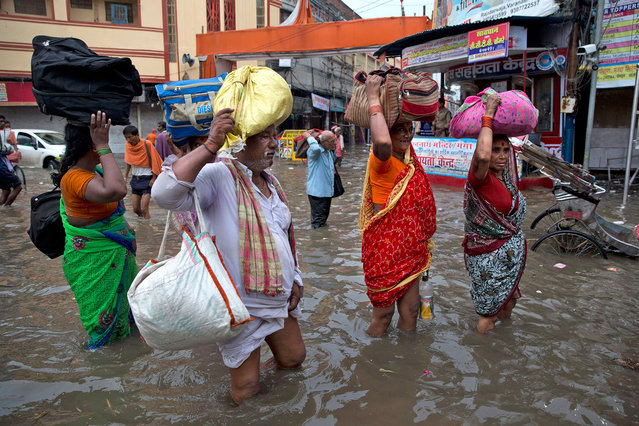 Indian devotees carry their luggage and wade through the flooded water in Varanasi, India, Friday, August 26, 2016. (Photo by Tsering Topgyal/AP Photo)