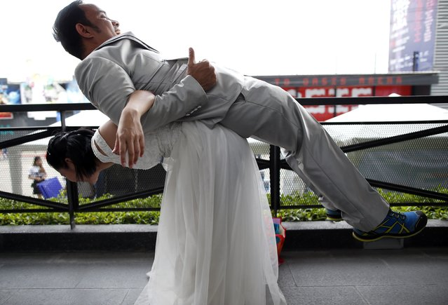 """A Thai bride-to-be and groom-to-be groom warm up before competing in the """"Running of the Brides"""" event in Bangkok, Thailand, 02 December 2017. (Photo by Rungroj Yongrit/EPA/EFE/Rex Features/Shutterstock)"""