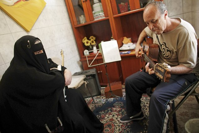 Gisele Marie, a Muslim woman and professional heavy metal musician, looks on as her teacher Marcelo (R) plays a guitar during a music class in Sao Paulo August 13, 2015. (Photo by Nacho Doce/Reuters)