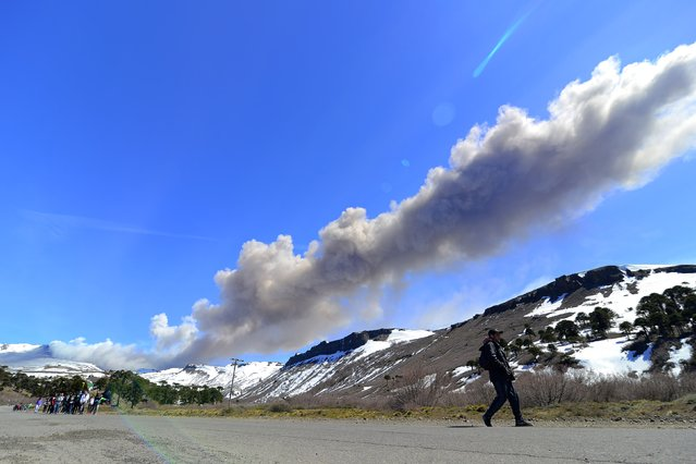 View of the Copahue volcano covered by clouds on October 12, 2014 from Caviahue, Neuquen, Argentina. The dark spot among the clouds is vapor and gases. (Photo by Francisco Negroni/AFP Photo)