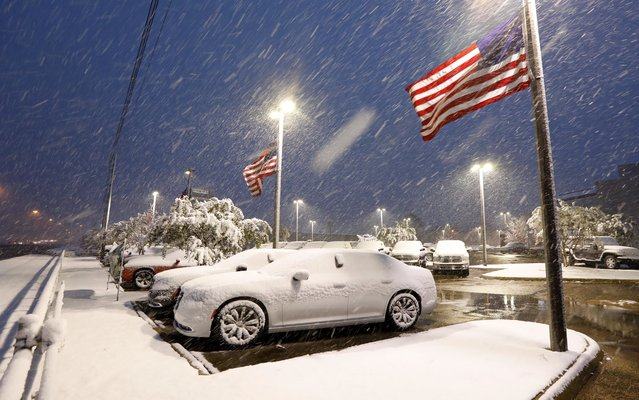 U.S. flags wave as snow falls, blanketing vehicles in a car sales lot, Friday, December 8, 2017, in Jackson, Miss. The forecast called for a wintry mix of precipitation across several Deep South states. (Photo by Rogelio V. Solis/AP Photo)