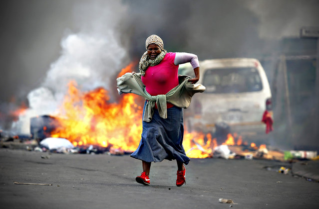 A South African resident of Masiphumelele runs past a burning barricade during a protest against the lack of policing in Masiphumelele, Cape Town, South Africa, 29 September 2015. According to local reports the protest was sparked by the court appearance 29 September of some residents arrested in connection with vigilante killings. (Photo by Nic Bothma/EPA)