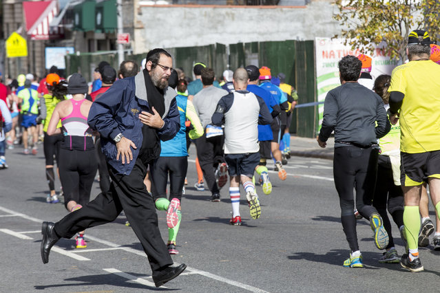 A man crosses the race course dodging runners, November 2, 2014. (Photo by Brendan McDermid/Reuters)