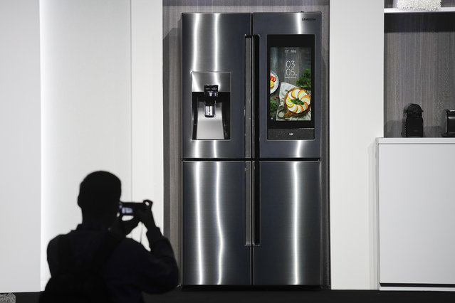 An attendee takes pictures of the new Samsung Family Hub smart refrigerator during a news conference at CES International, Monday, January 8, 2018, in Las Vegas. (Photo by Jae C. Hong/AP Photo)