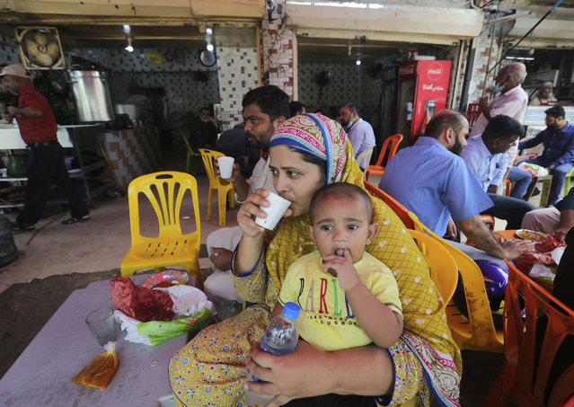 People eat at a restaurant following an ease in restrictions that had been imposed to help control the coronavirus, in Karachi, Pakistan, Monday, August 10, 2020. Pakistan's daily virus infection rate has stayed under 1,000 for more than four weeks prompting the government to further ease restrictions for restaurants, parks, gyms and cinemas. (Photo by Fareed Khan/AP Photo)