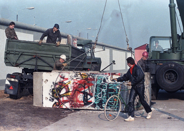 East German workers remove concrete parts of the Berlin Wall and load them onto trucks at the recently opened border crossing point at Potsdam Platz, November 9, 1989. (Photo by Wolfgang Rattay/Reuters)