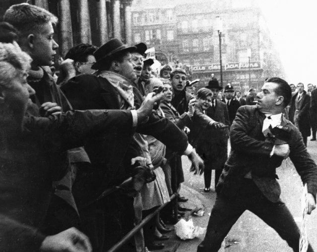 A Flemish demonstrator, one of thousands who gathered for a march through Brussels to protest against what the Flemings call their subjucation by the French-speaking Walloons, draws back as he is jeered by a crowd of Walloons on the pavement in a Brussels Street, on October 14, 1962. The Flemish demonstrators clashed with Walloon counter demonstrators as riot police sought to maintain order. (Photo by AP Photo)