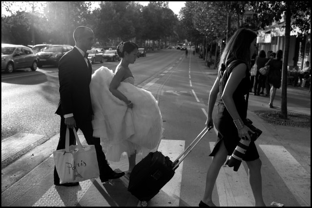 Crossing the threshold in Paris. An American couple from Brooklyn, Glenn and Linda, cross the street after their wedding yesterday. They came to Paris for their big day and were headed to celebrate their wedding diner at a restaurant on the Eiffel Tour. (Photo and comment by Peter Turnley)
