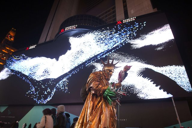 A man dressed up as the Statue of Liberty walks in front of a new digital advertising screen in Times Square, New York, November 18, 2014. (Photo by Carlo Allegri/Reuters)
