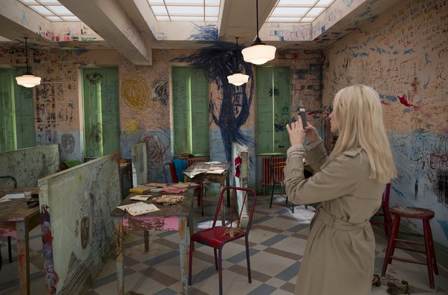 """A woman photographs Robin Brown's installation """"The Asylum"""" which was inspired by the work of artist Jean Dubuffet, at the Frieze Masters show in London, Britain October 16, 2015. (Photo by Neil Hall/Reuters)"""