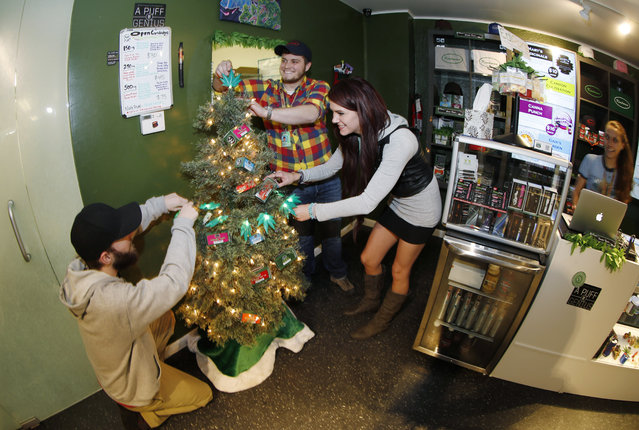 In this photograph taken on Thursday, November 20, 2014, bud tenders from left John Satterfield, Maxwell Bradford and Emma Attolini decorate a Christmas tree in holiday display at a recreational marijuana shop in northwest Denver. Colorado's marijuana retailers are taking a page out of the playbook of traditional retialers to market their products to holiday shoppers. (Photo by David Zalubowski/AP Photo)