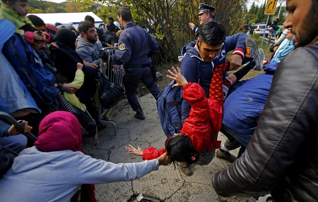 Migrants hold a child as a crowd of migrants attempts to break through a cordon in front of a makeshift camp near the Austrian border in Sentilj, Slovenia October 20, 2015. (Photo by Leonhard Foeger/Reuters)