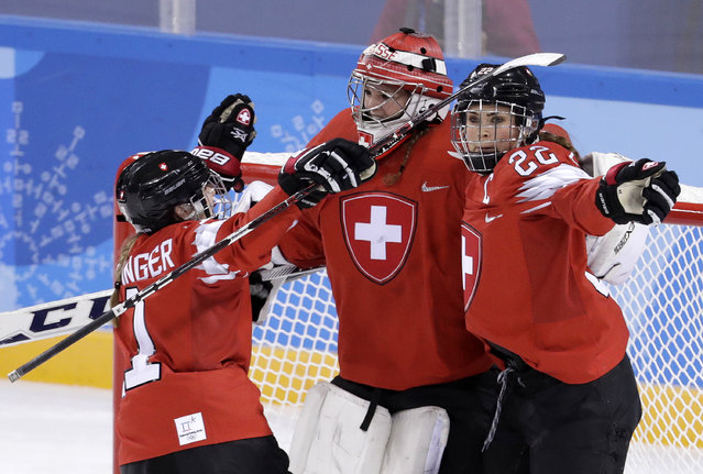 Sabrina Zollinger (11), goalie Florence Schelling (41) and Livia Altmann (22), of Switzerland, celebrate after the preliminary round of the women's hockey game against Japan at the 2018 Winter Olympics in Gangneung, South Korea, Monday, February 12, 2018. (Photo by Julio Cortez/AP Photo)