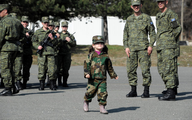A Kosovo Albanian child dressed in a military costume takes part in a ceremony in Pristina on March 5, 2013 marking the 15th anniversary of the killing of Kosovo Liberation Army (KLA) commander Adem Jashari. Jashari was among 45 members of his family killed by Serb security forces in the vilage of Prekaz some 40 kms west of the Kosovo capital Pristina, sparking a full-blown rebel insurgency. (Photo by Armend Nimani/AFP Photo)