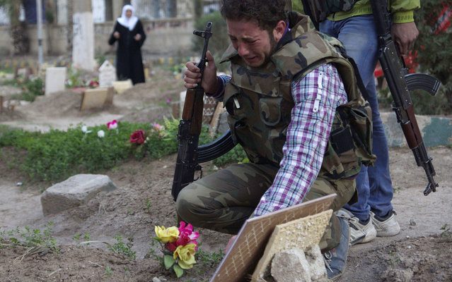 A Free Syrian Army fighter mourns at the grave of his father who was killed by what activists said was shelling by forces loyal to Syria's President Bashar al-Assad, in a public park that has been converted into a makeshift graveyard in Deir el-Zor, on March 12, 2013. (Photo by Khalil Ashawi/Reuters)