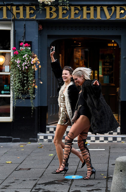Two women walk past The Beehive pub in the Grassmarket following pubs closing at 6pm on October 9, 2020 in Edinburgh, Scotland. Pubs and restaurants in the central belt of Scotland close their doors for a fortnight while from 6pm in tough new coronavirus measures set out by the Scottish Government. (Photo by Jeff J. Mitchell/Getty Images)