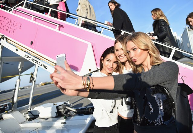 (L-R) Victoria's Secret Model Lily Aldridge, Behati Prinsloo and Karlie Kloss take a picture before they depart for London for the 2014 Victoria's Secret Fashion Show at JFK Airport on November 30, 2014 in New York City. (Photo by Mike Coppola/Getty Images for Victoria's Secret)