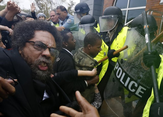 Activist Cornel West (L) is knocked over during a scuffle with police during a protest at the Ferguson Police Department in Ferguson, Missouri, in this October 13, 2014 file photo. (Photo by Jim Young/Reuters)