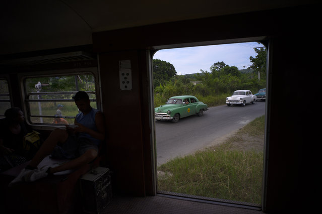 In this August 26, 2015 photo, antique American cars wait for an electric Hershey train to pass through the Casablanca municipality of Havana, Cuba. The train connects Casablanca to the city of Matanzas. In 1916 the Corporation of Pennsylvania Hershey built a network of electric railways to transport their products and workers to the Hershey sugar factory, just east of the capital. (Photo by Ramon Espinosa/AP Photo)